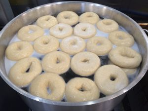 Bagels are boiled, or steamed, to maintain the hole during baking. It also gives the finished product the look and bite we expect in a bagel.