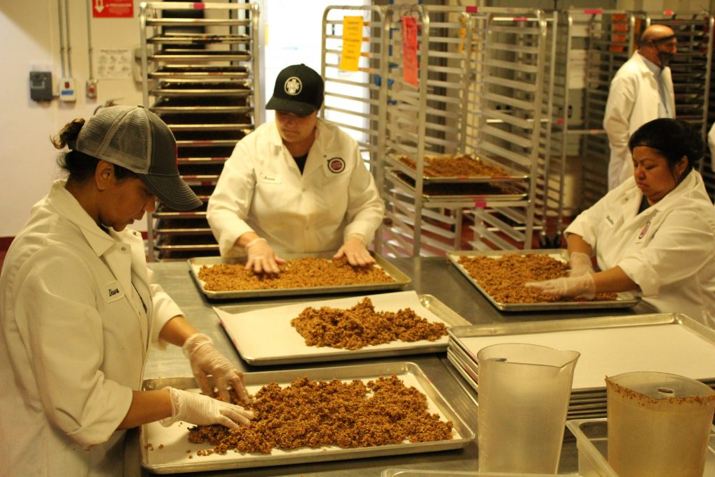 Staff from CommonWealth Kitchen prepare HealthSense wheat cluster granola for the oven.