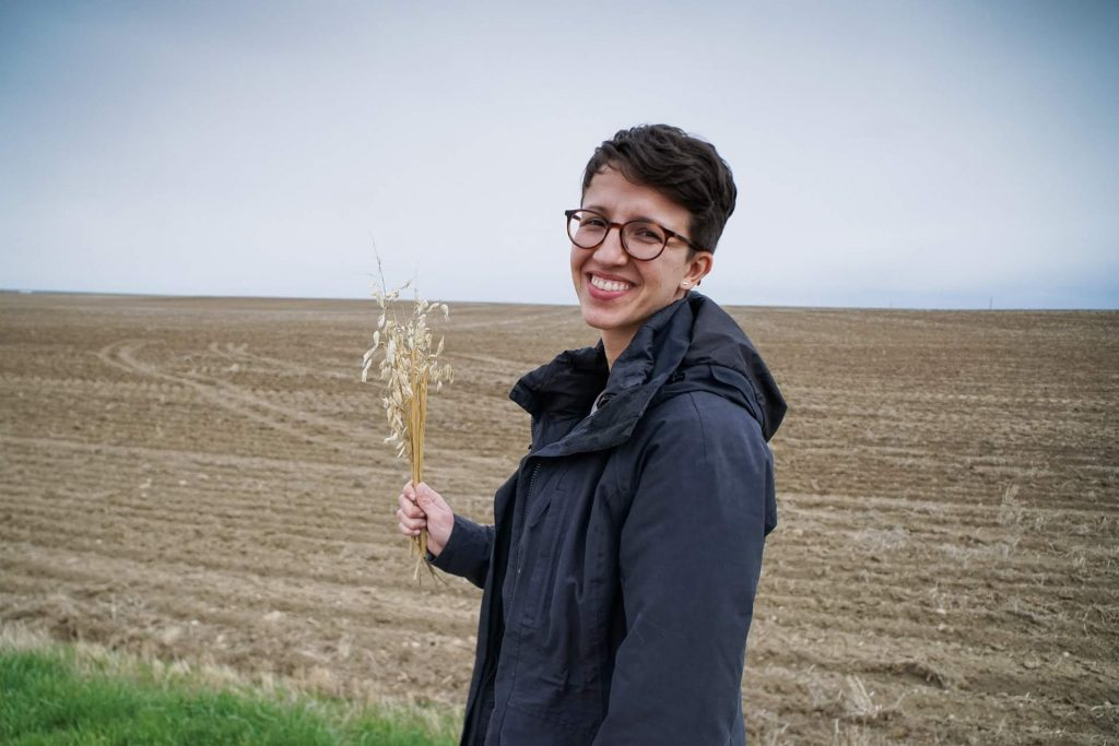 One of the MIT students with SowNaked oats in a field in Montana.